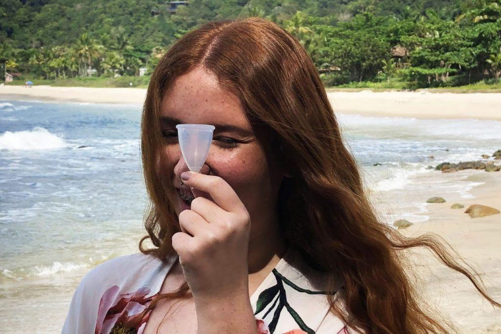 menina com coletor menstrual na praia